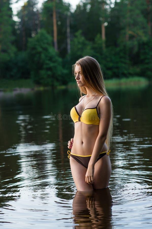 Adolescente delgado encantador de la muchacha en el traje de baño de moda que se coloca en agua fotografía de archivo libre de regalías