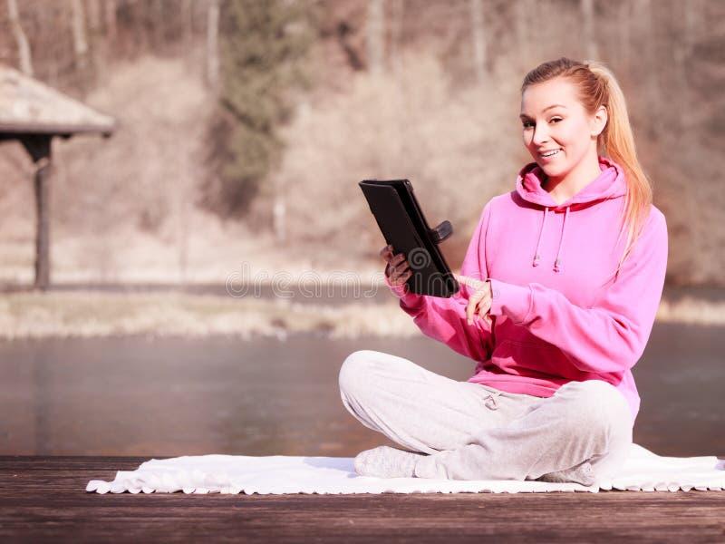 Adolescente della donna in tuta sportiva facendo uso della compressa sul pilastro all'aperto fotografia stock