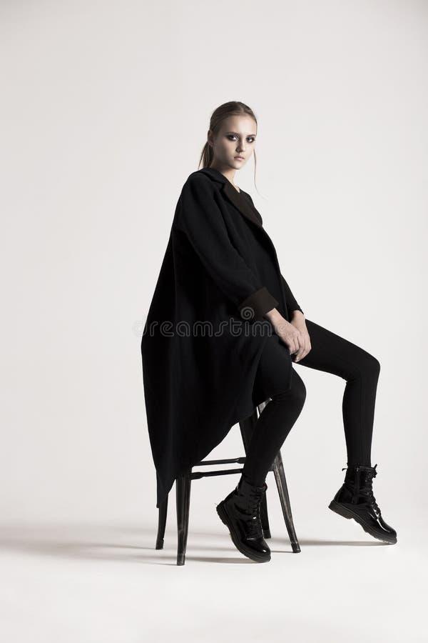 Adolescente della ragazza nello studio che si siede su una sedia immagini stock libere da diritti