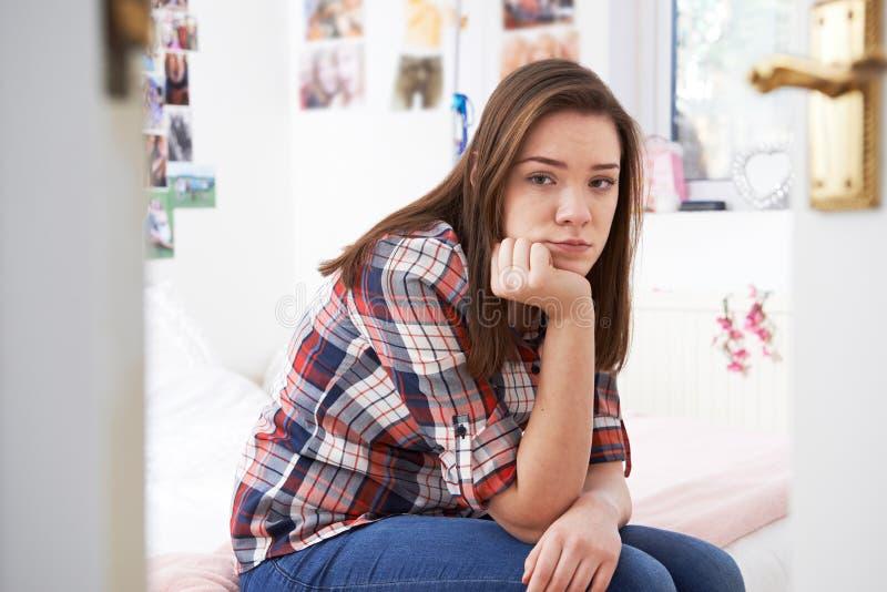 Adolescente depresso che si siede nella camera da letto immagine stock libera da diritti