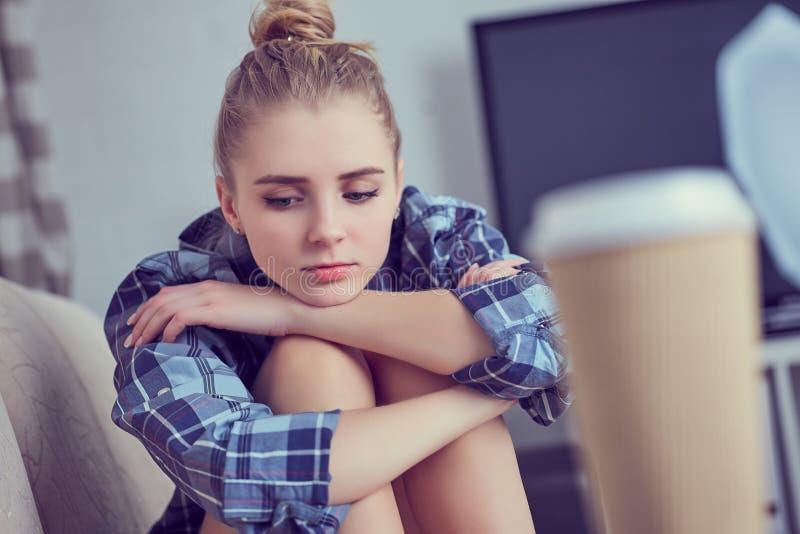 Adolescente depresso solo infelice a casa, sta sedendosi sullo strato e propped la sua testa con i suoi piedi fotografia stock libera da diritti