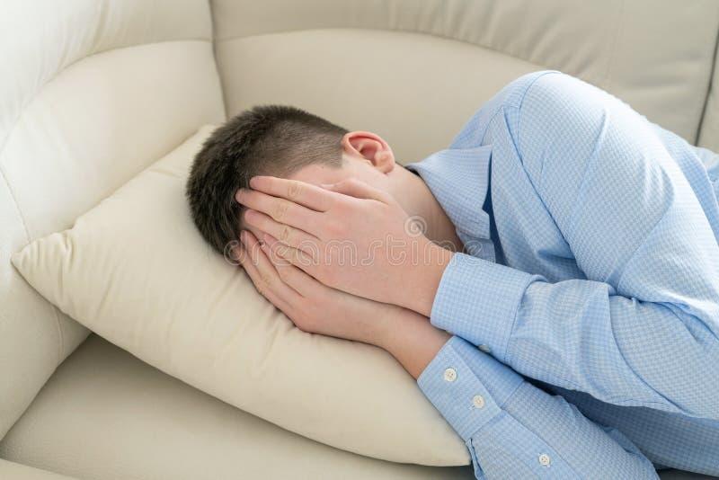 Adolescente deprimido que encontra-se no sof? que cobre sua cara com suas m?os foto de stock