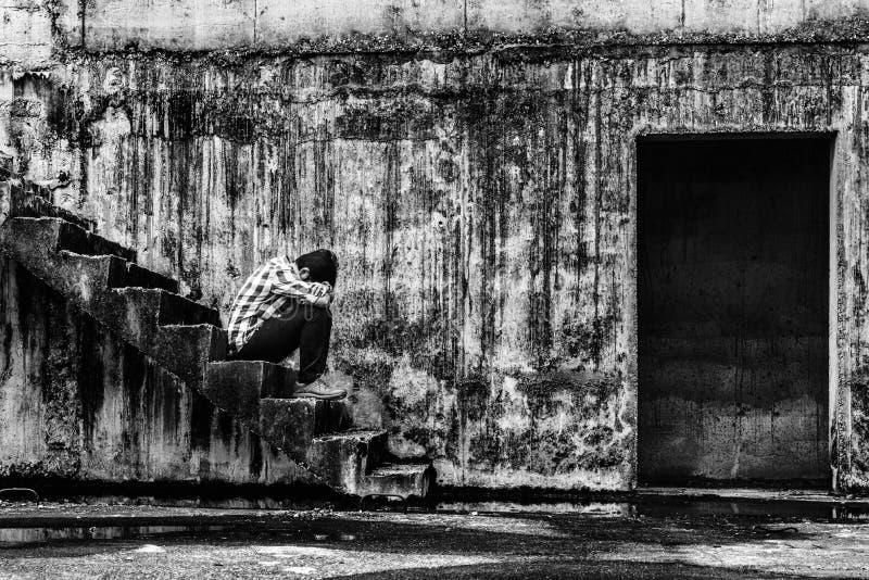 Adolescente deprimido que se sienta en la escalera en el edificio abandonado espeluznante fotografía de archivo libre de regalías