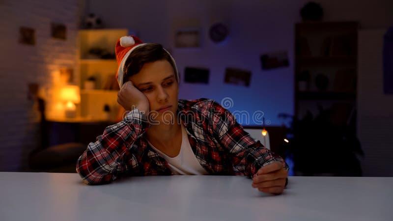 Adolescente deprimido s? no chap?u de Santa que comemora o ano novo que guarda a luz de Bengal imagens de stock royalty free