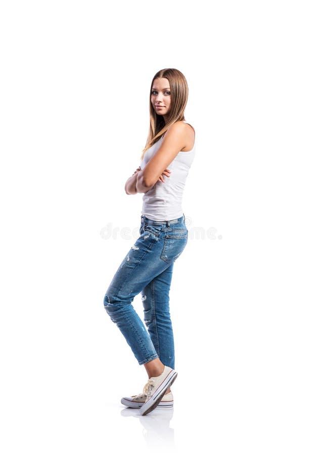 Adolescente derecho en los vaqueros y la camiseta blanca, aislados imagenes de archivo