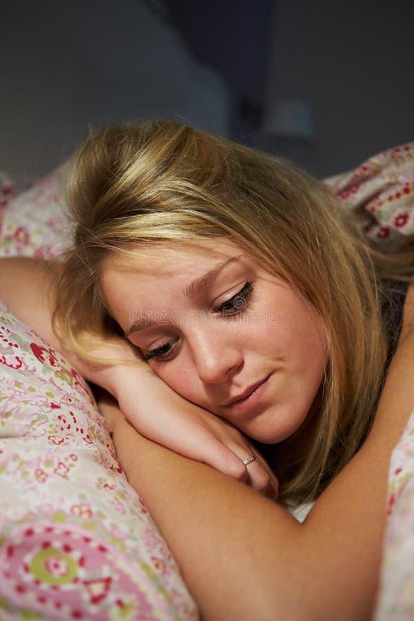 Adolescente despierto en la cama que sufre con insomnio imagenes de archivo