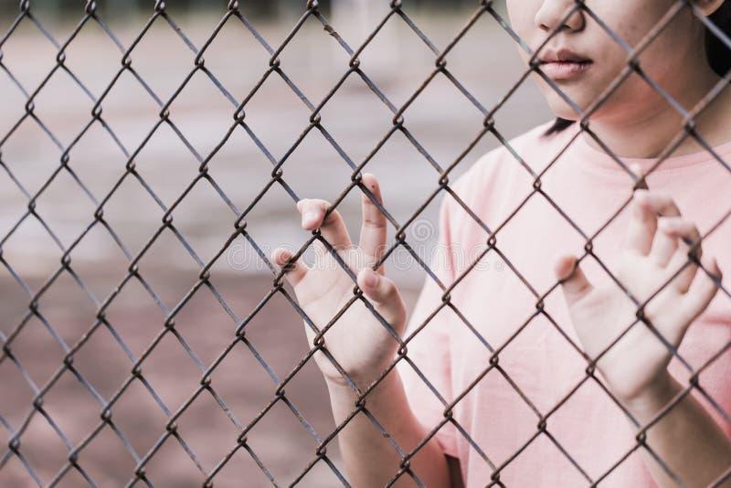 Adolescente detrás de la jaula o de la mujer encarcelada fotografía de archivo libre de regalías