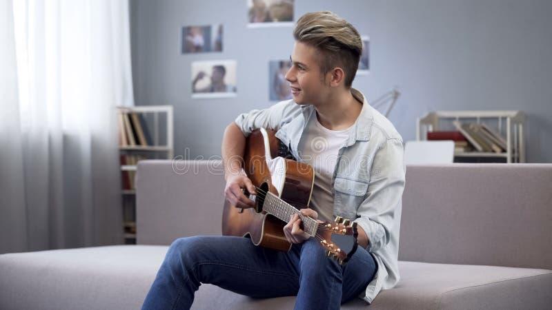 Adolescente di talento che gioca chitarra, tipo dell'istituto universitario che gode della melodia per la sua nuova canzone fotografia stock