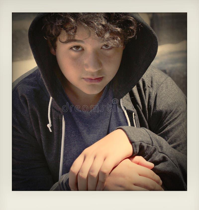 Adolescente disturbato triste della scuola che posa seduta all'aperto sulla via che vi esamina - vicino su del fronte con i color fotografia stock