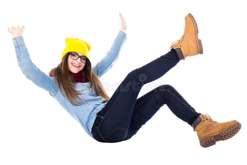 Adolescente divertido que cae abajo en la ropa del invierno aislada en wh fotos de archivo