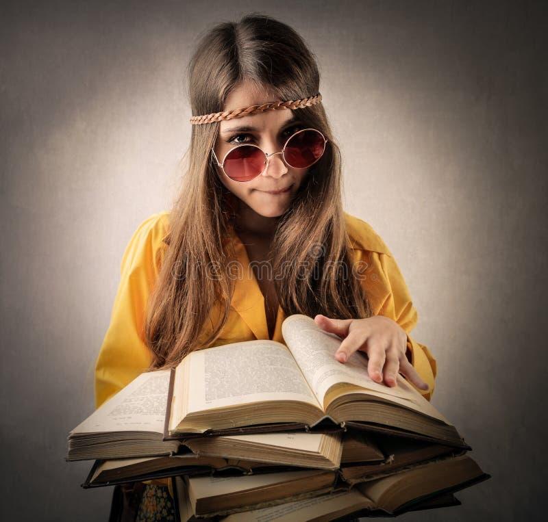 Adolescente do hippy que lê muitos livros fotografia de stock