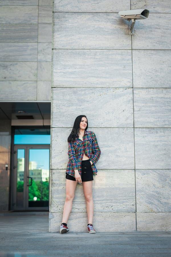 Adolescente do moderno que está contra a parede na rua fotografia de stock