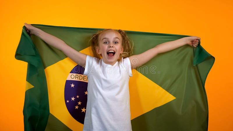 Adolescente doce que cheering para a equipe brasileira favorita, guardando a bandeira nacional fotografia de stock royalty free