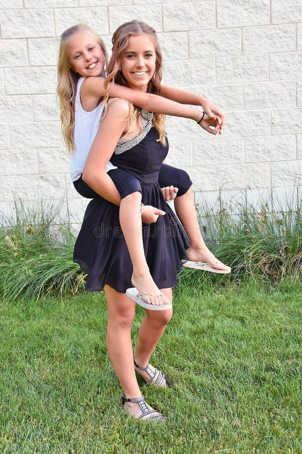 Adolescente donnant à soeur un tour de ferroutage image libre de droits