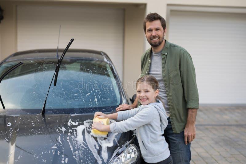 Adolescente e pai que lavam um carro em um dia ensolarado fotos de stock