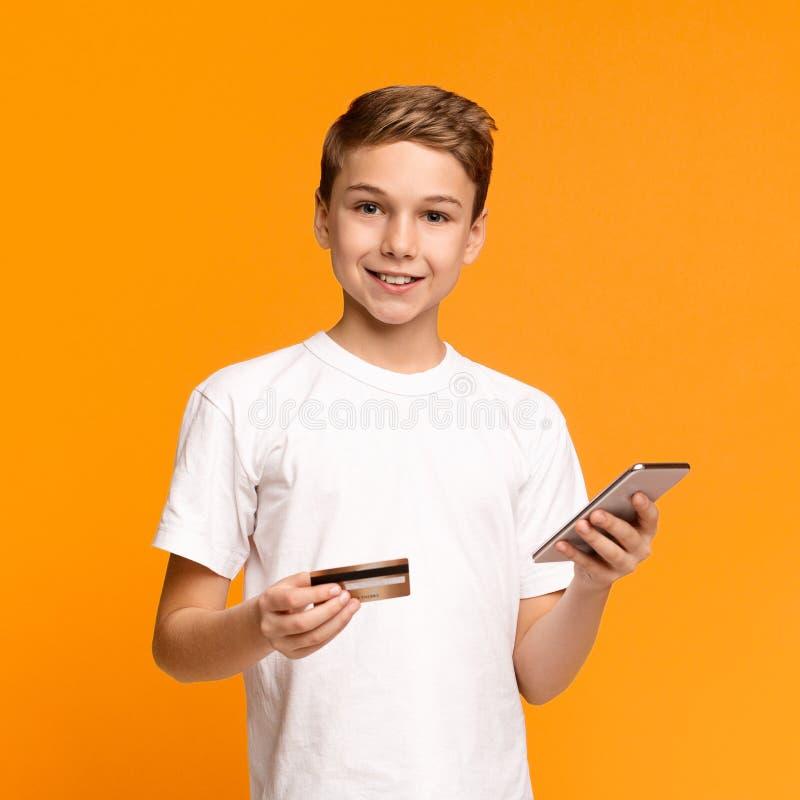 Adolescente educado usando aplicación móvil y tarjeta de crédito fotografía de archivo