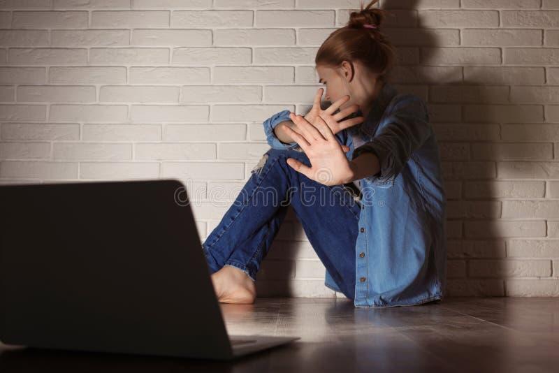 Adolescente effrayée avec l'ordinateur portable sur le plancher Danger d'Internet photo libre de droits