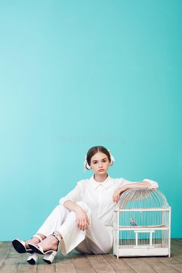 adolescente elegante no branco com o papagaio na gaiola imagens de stock royalty free