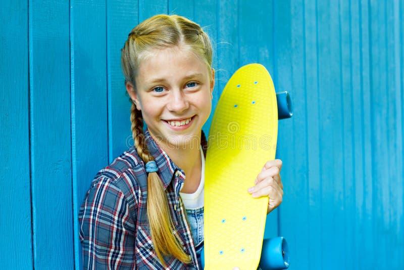 Adolescente elegante ropa de los vaqueros de un verano que lleva, con el monopat?n divirti?ndose en ciudad sobre fondo azul color imagenes de archivo