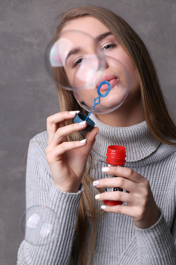 Adolescente em bolhas de sopro do jérsei Fim acima Fundo cinzento fotos de stock royalty free