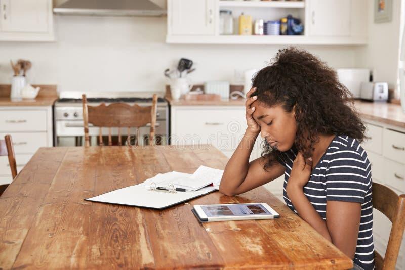 Adolescente em casa que usa a tabuleta de Digitas que está sendo tiranizada na linha fotografia de stock royalty free