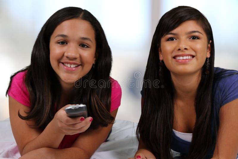 Adolescente em sua cama com amigo fotografia de stock royalty free