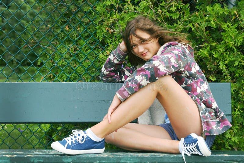 Adolescente em um banco imagens de stock