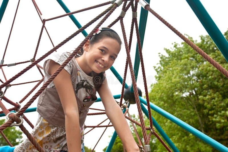 Adolescente em um frame de escalada em um parque imagem de stock