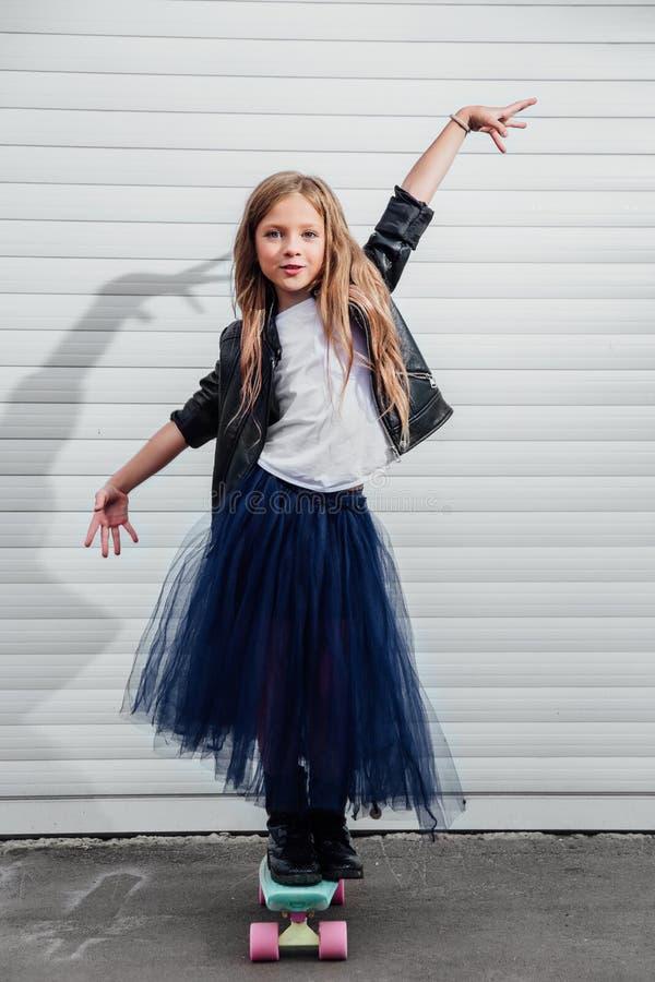 Adolescente em um skate contra uma parede branca de uma porta da garagem fotografia de stock royalty free