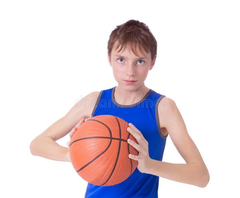 Adolescente em um t-shirt azul com a bola para o basquetebol Isolado no fundo branco fotos de stock
