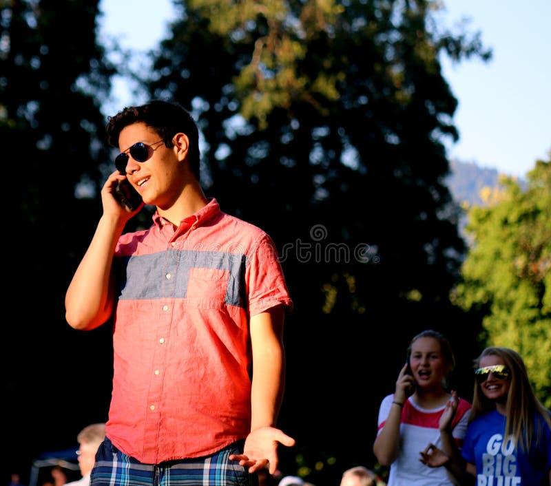 Adolescente em um telefone celular com espectador imagem de stock