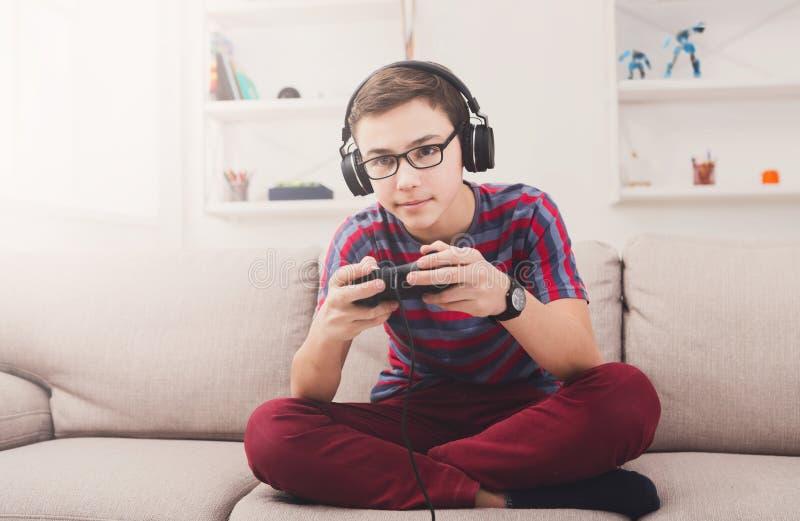 Adolescente emocionado que juega al videojuego en casa imagen de archivo libre de regalías