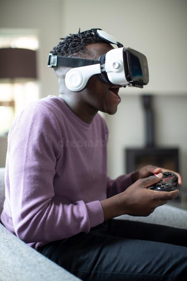 Adolescente emocionado que juega al videojuego en casa que lleva las auriculares de la realidad virtual imagen de archivo libre de regalías