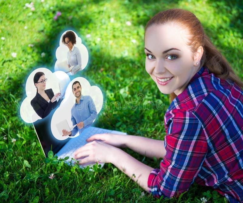 Adolescente employant l'ordinateur portable dans le parc et les nuages avec ses amis photographie stock