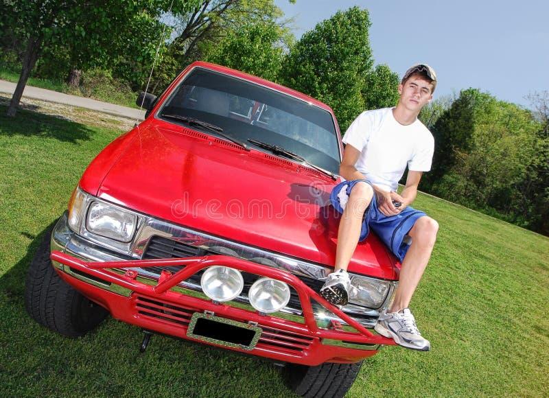 Adolescente en el capo motor del carro fotografía de archivo
