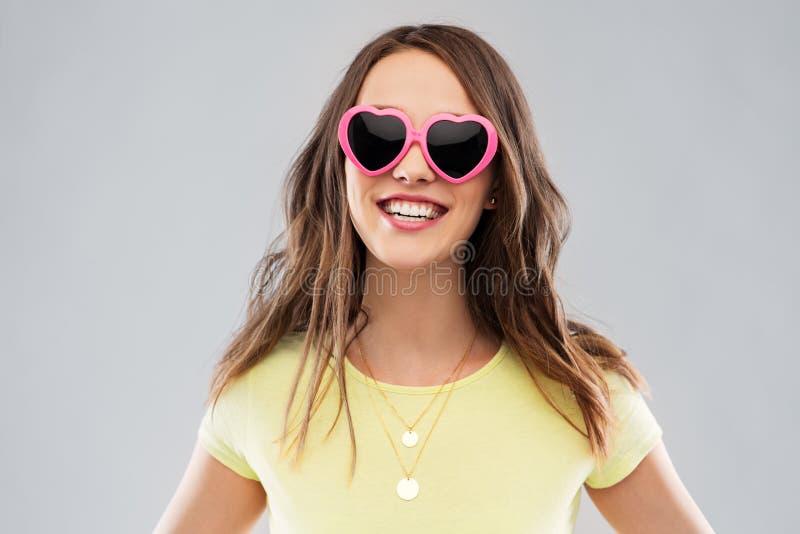 Adolescente en gafas de sol en forma de coraz?n imagen de archivo