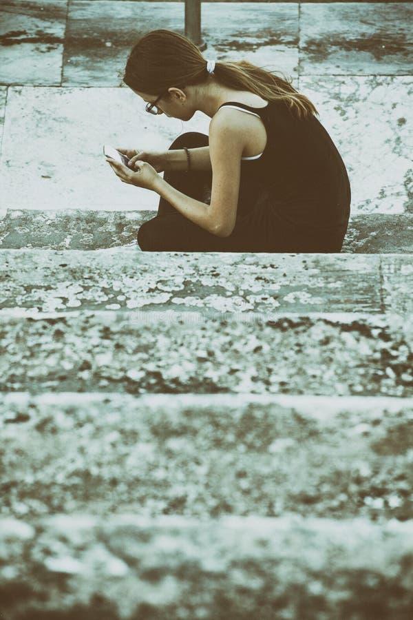 Adolescente en la ciudad con el smartphone imagenes de archivo