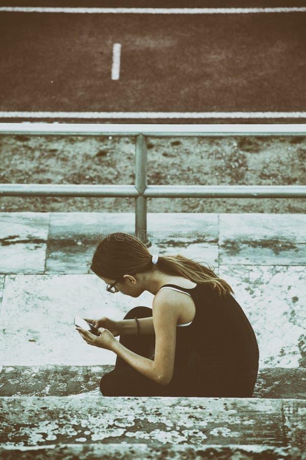 Adolescente en la ciudad con el smartphone imagen de archivo libre de regalías