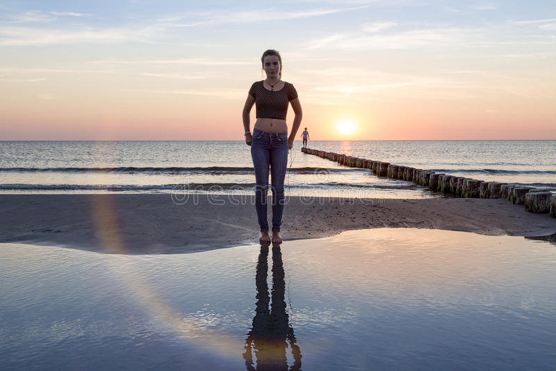 Adolescente en la playa en la puesta del sol fotos de archivo libres de regalías