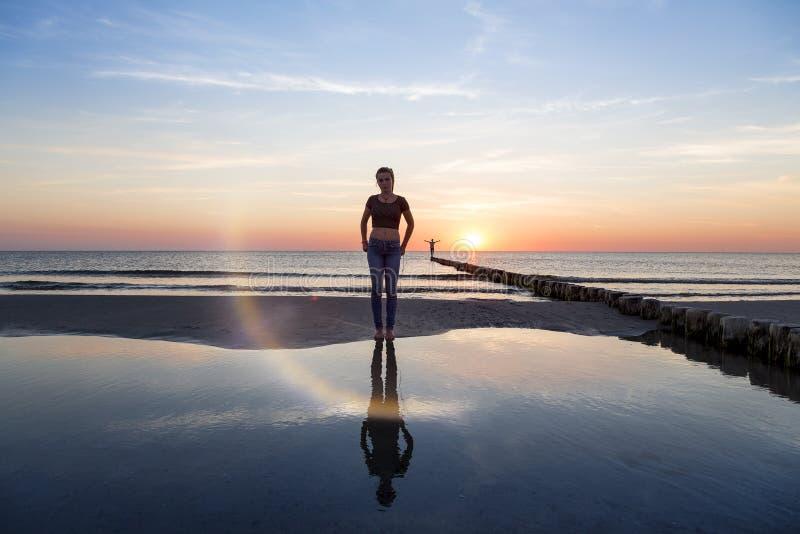 Adolescente en la playa en la puesta del sol fotos de archivo