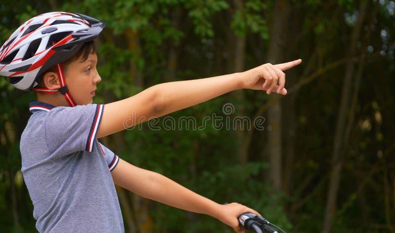 Adolescente en la situación protectora del casco sobre mi bici y mostrar los puntos de referencia fotos de archivo libres de regalías