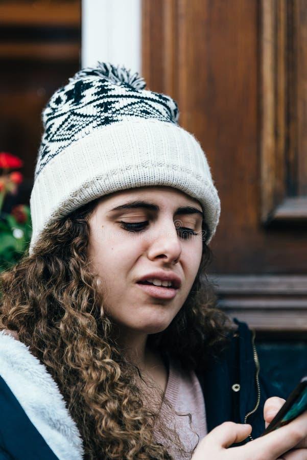 Adolescente en sombrero de punto con la expresión facial extraña que manda un SMS a los wi foto de archivo