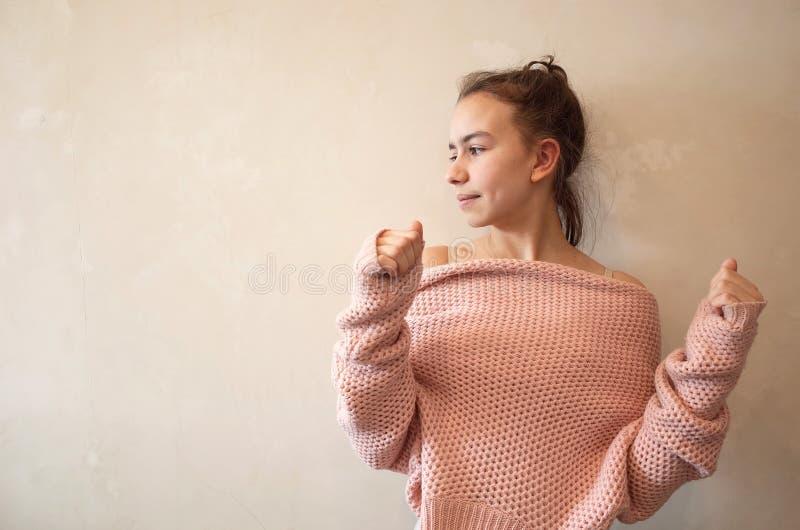 Adolescente en suéter hecho punto rosado fotos de archivo