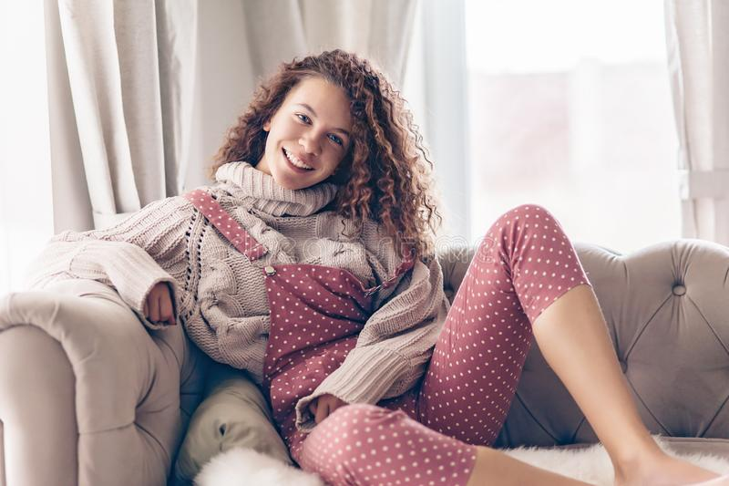Adolescente en suéter y mono en un sofá fotografía de archivo
