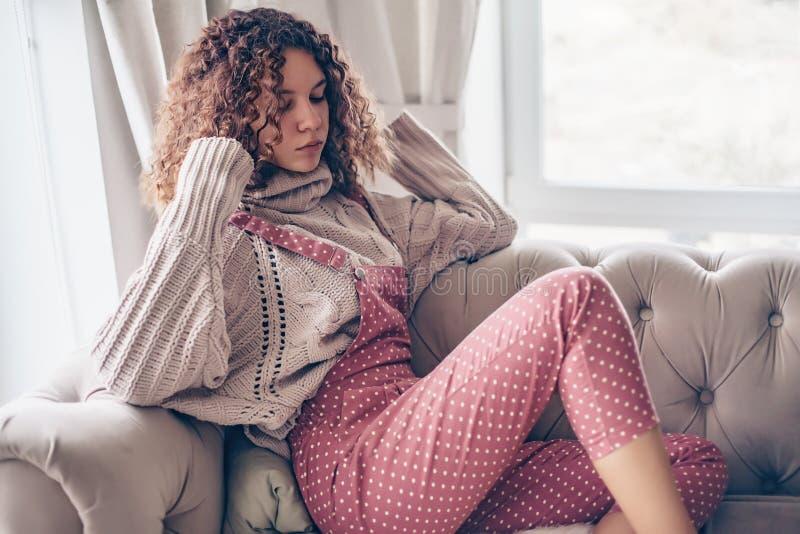 Adolescente en suéter y mono en un sofá imagenes de archivo