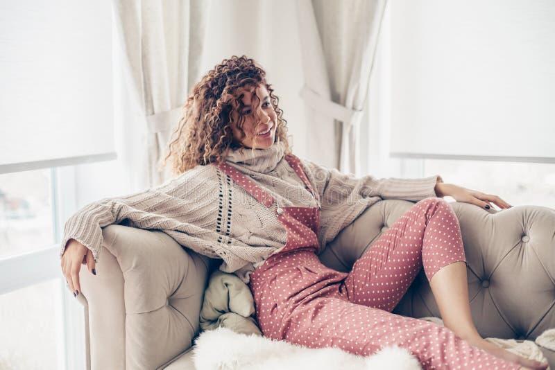 Adolescente en suéter y mono en un sofá imagen de archivo