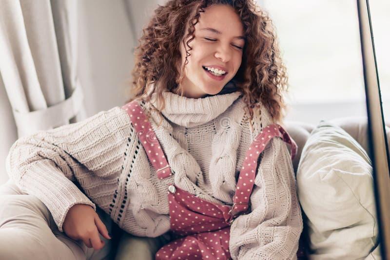 Adolescente en suéter y mono en un sofá fotos de archivo