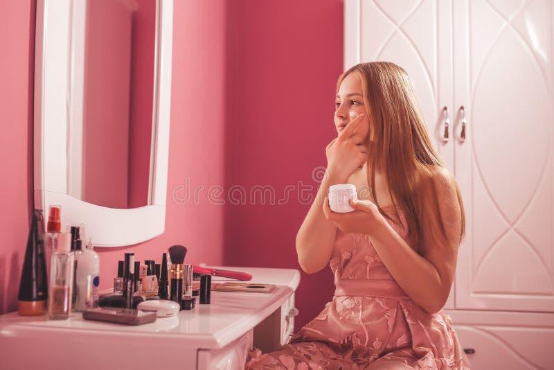 Adolescente en un vestido que pone la crema en la cara, preparándose para el maquillaje imagen de archivo