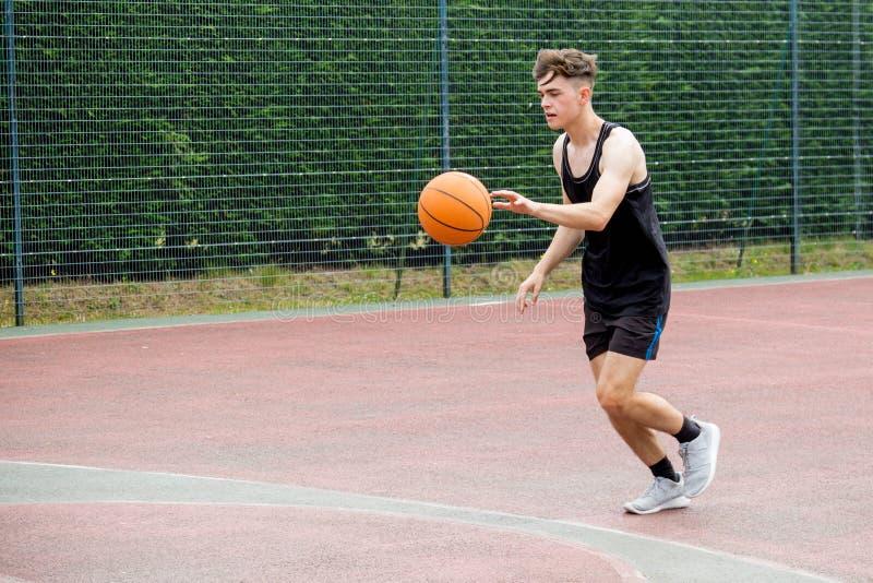 Adolescente en una cancha de básquet fotografía de archivo