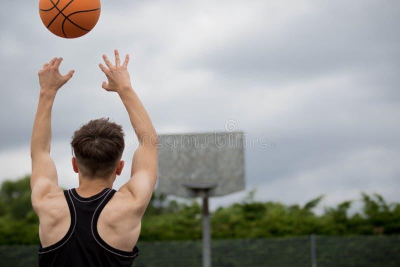Adolescente en una cancha de básquet imagen de archivo libre de regalías